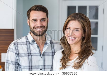 Close-up portrait of smiling young couple at home