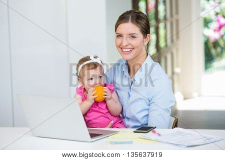 Happy woman sitting with baby by table at home