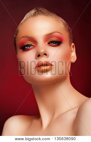 Woman With Art Stage Make Up On Red Background