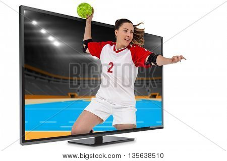Sportswoman throwing a ball against handball field indoor