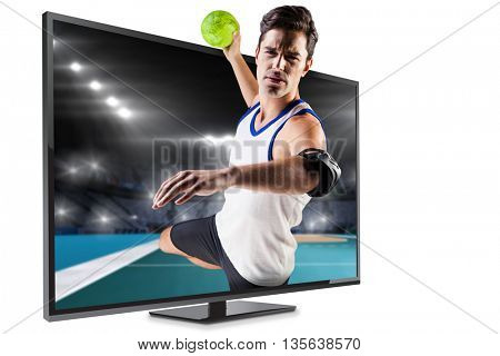 Portrait of athlete man throwing a ball against handball field indoor