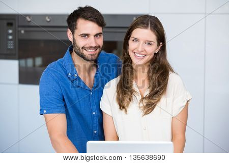 Portrait of happy couple with laptop standing at home
