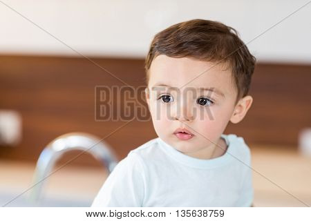Close-up of cute baby boy looking away at home