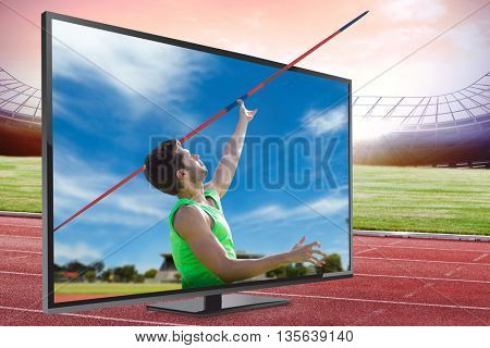 Athletic man throwing a javelin against view of running track