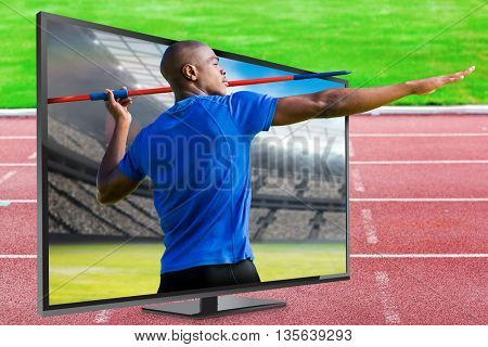 Profile view of sportsman practising javelin throw against view of a stadium