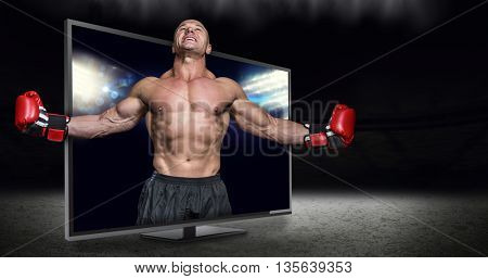 Boxer with arms outstretched against view of spotlights
