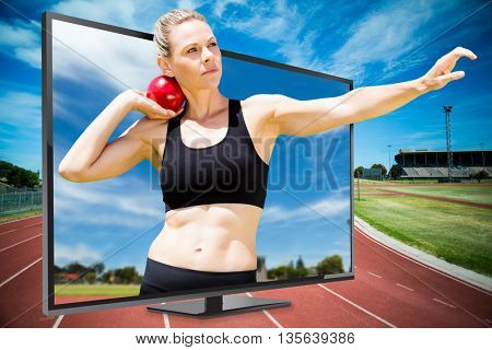 Front view of sportswoman practising shot put against view of running track