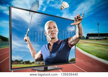 Badminton player playing badminton against view of running track
