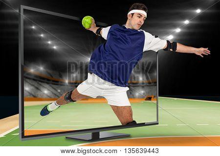 Sportsman throwing a ball against handball field indoor