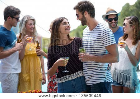 Group of friends holding a glass of cocktail and beer on a sunny day