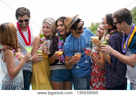 Group of friends wearing a garland and holding a glass of cocktail on a sunny day