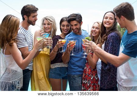 Group of friends holding a glass of cocktail near the pool on a sunny day