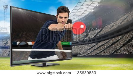 Portrait of male athlete playing table tennis against view of a stadium