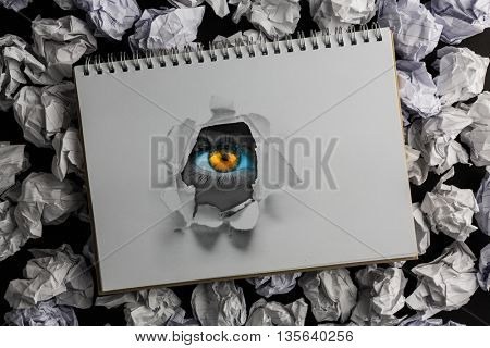 Bright orange eyes on female face against view of a notebook