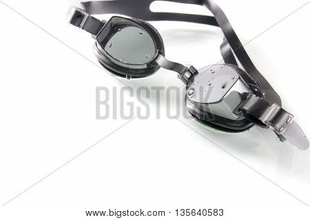 black swimming glasses on white background with water drop and shadow reflex selective focus