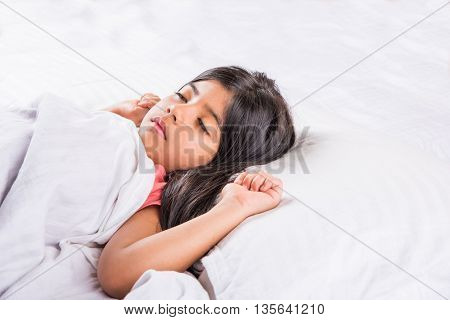 cute Indian Girl sleeping over white pillow, small asian girl sleeping on bed