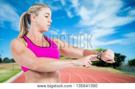 Female athlete using her smart watch against high angle view of track