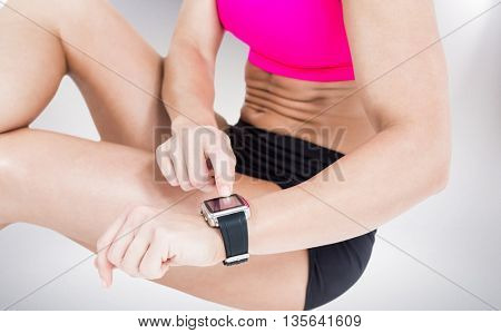 Female athlete sitting and using her smart watch against grey background