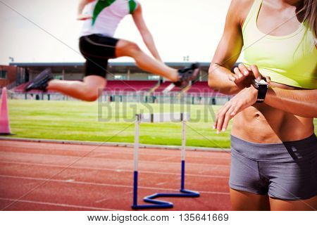 Sporty woman looking her watch against serious male athlete jumping above hedge during a race