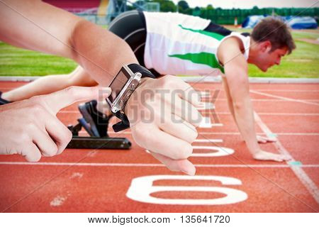Female athlete using her smart watch against handsome sprinter on the starting line putting his foot in the s