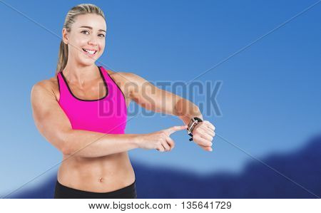 Female athlete using her smart watch against scenic view of blue sky