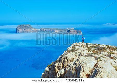 man runs on a cliff against a blue sea