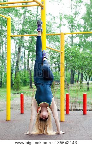 sexy young fitness girl on the street gym. Blond fitness woman in sportswear with a perfect body fitness workout on the street to do the exercises on the horizontal bar. Handstand.