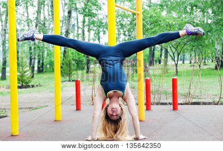 sexy young fitness girl on the street gym. Blond fitness woman in sportswear with a perfect body fitness workout on the street to do the exercises on the horizontal bar. Handstand and twine