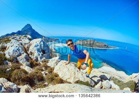 man runs on a cliff against a blue sea.