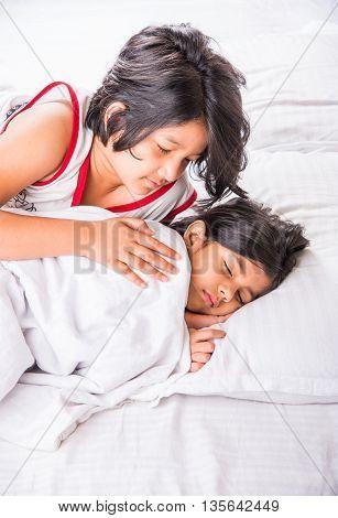 indian cute little siblings or sisters or friends sleeping in a bedroom