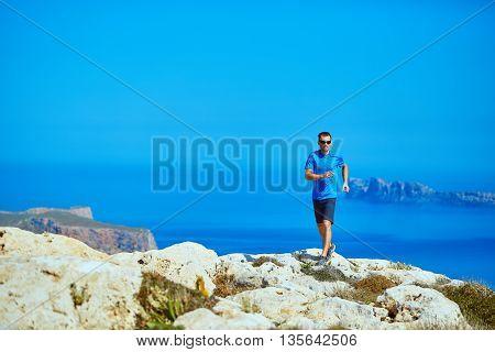 man runs on a cliff against a blue sky and sea