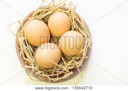Eggs in wooden bowl with rice straw isolated on white background