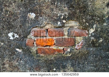 wall with plaster cracked and worn by time and neglect with red brick and gray stone walls