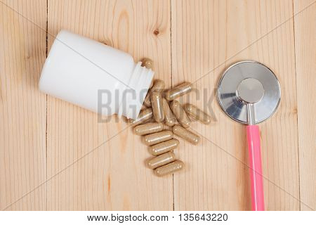 herb capsules and stethoscope on wood table
