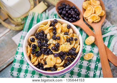 cornflake with fresh ripe bilberry and milk in crockery dish