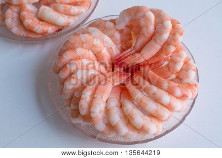 Fresh pink cooked prawn shrimps on a white background
