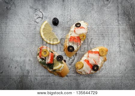 Tasty various italian sandwiches with seafood against rustic wooden background. Crostini with cheese crab sticks lemon and sliced olives horizontal top view