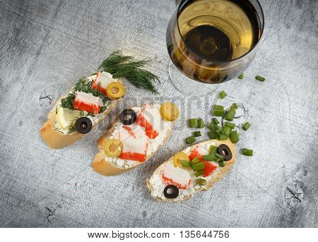 Tasty various italian sandwiches with seafood against rustic wooden background. Crostini with cheese crab sticks lemon sliced olives herbs and glass of wine horizontal top view