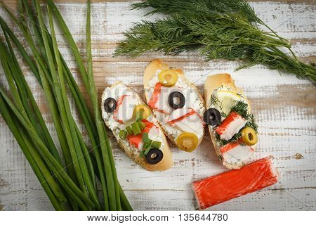 Tasty various italian sandwiches with seafood against rustic wooden background. Crostini with cheese crab sticks lemon sliced olives herbs and crab stick horizontal top view