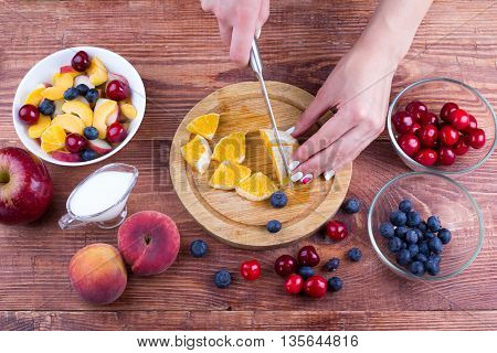 The person cooks fruit salad. Concept of a healthy lifestyle and food