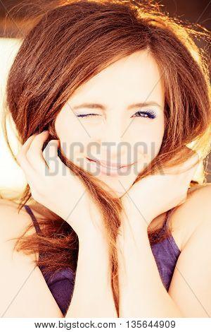 Winking beautiful Woman. Happy Smiling Fashion Model