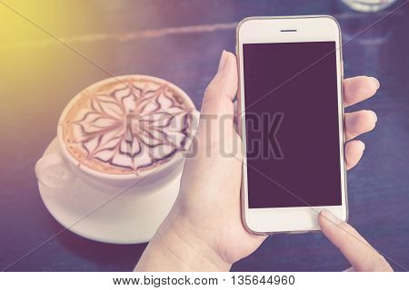 Close up of a woman using mobile smart phone in coffee shop with Soft Focus Color Filtered background.