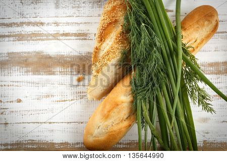 Crusty fresh seasoned baguette with sesame with fresh herbs on rustic wooden background horizontal top view with copy space