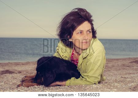 Portrait of dreaming woman with a dog on the beach. Toned image.