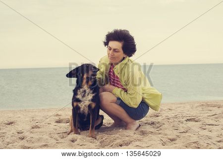 Happy woman playing with a dog on the beach. Toned image.
