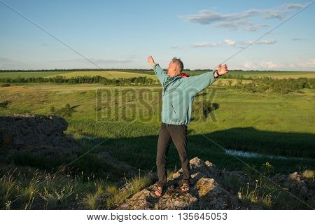 Happy man stands on a cliff in the prairie his arms outstretched looking up at the sky and laughs. Sunset in a prairie desert. Azov steppes Ukraine.
