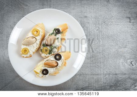 Tasty various italian sandwiches with seafood against rustic wooden background. Crostini with cheese mussels and sliced olives on white plate with copy space horizontal top view