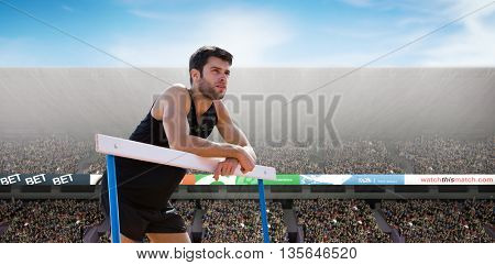 Athletic man pressed on a hurdle posing against view of a stadium