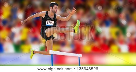 Athletic man practicing show jumping against blurry football pitch with crowd