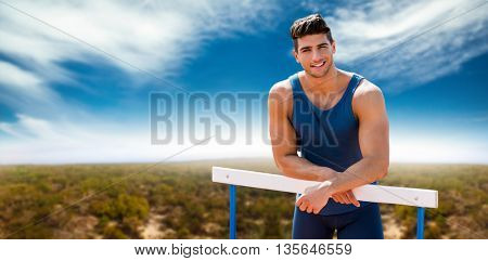 Portrait of sportsman is smiling and posing on a hurdle against view of an empty field